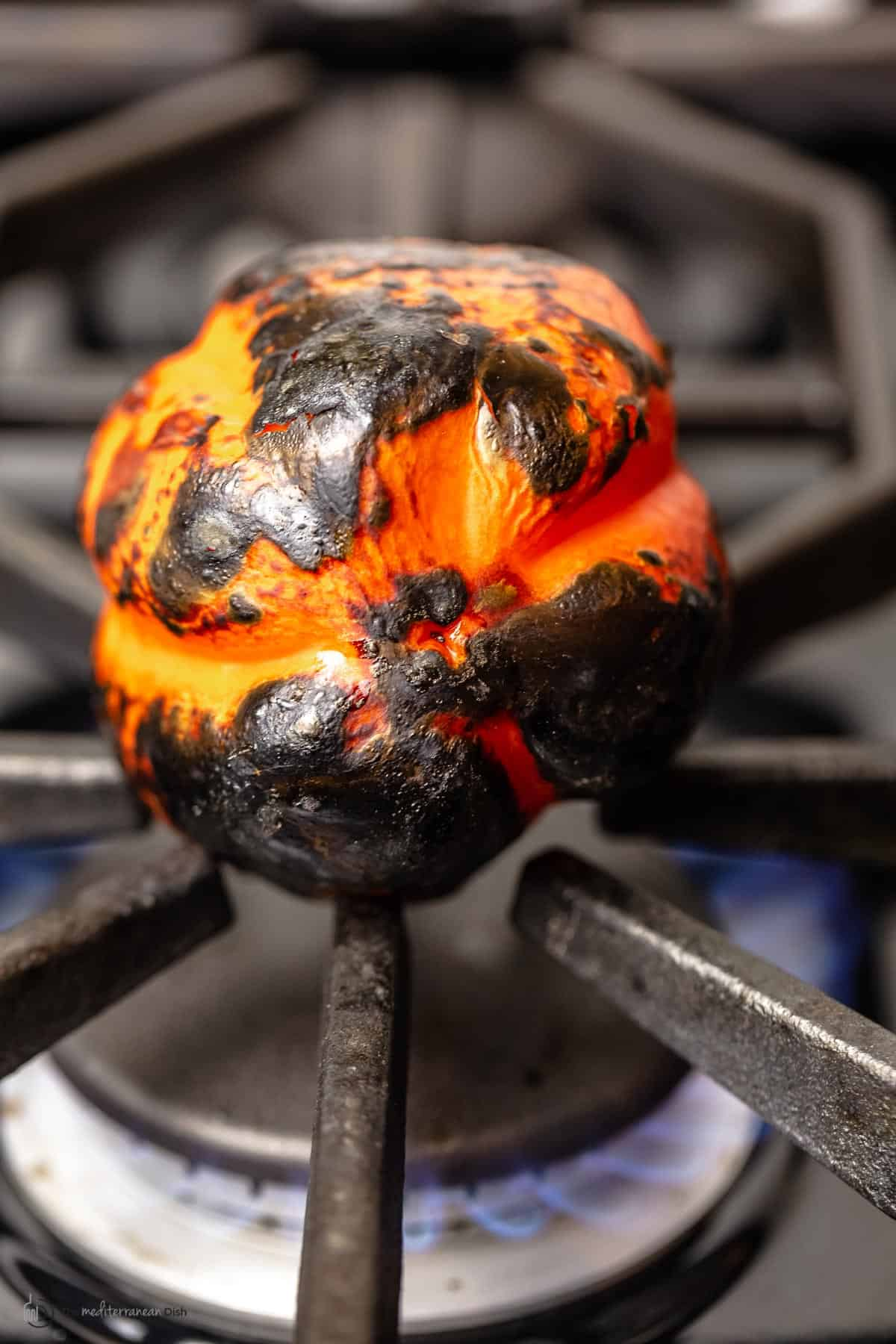 An orange bell pepper roasting on the stovetop