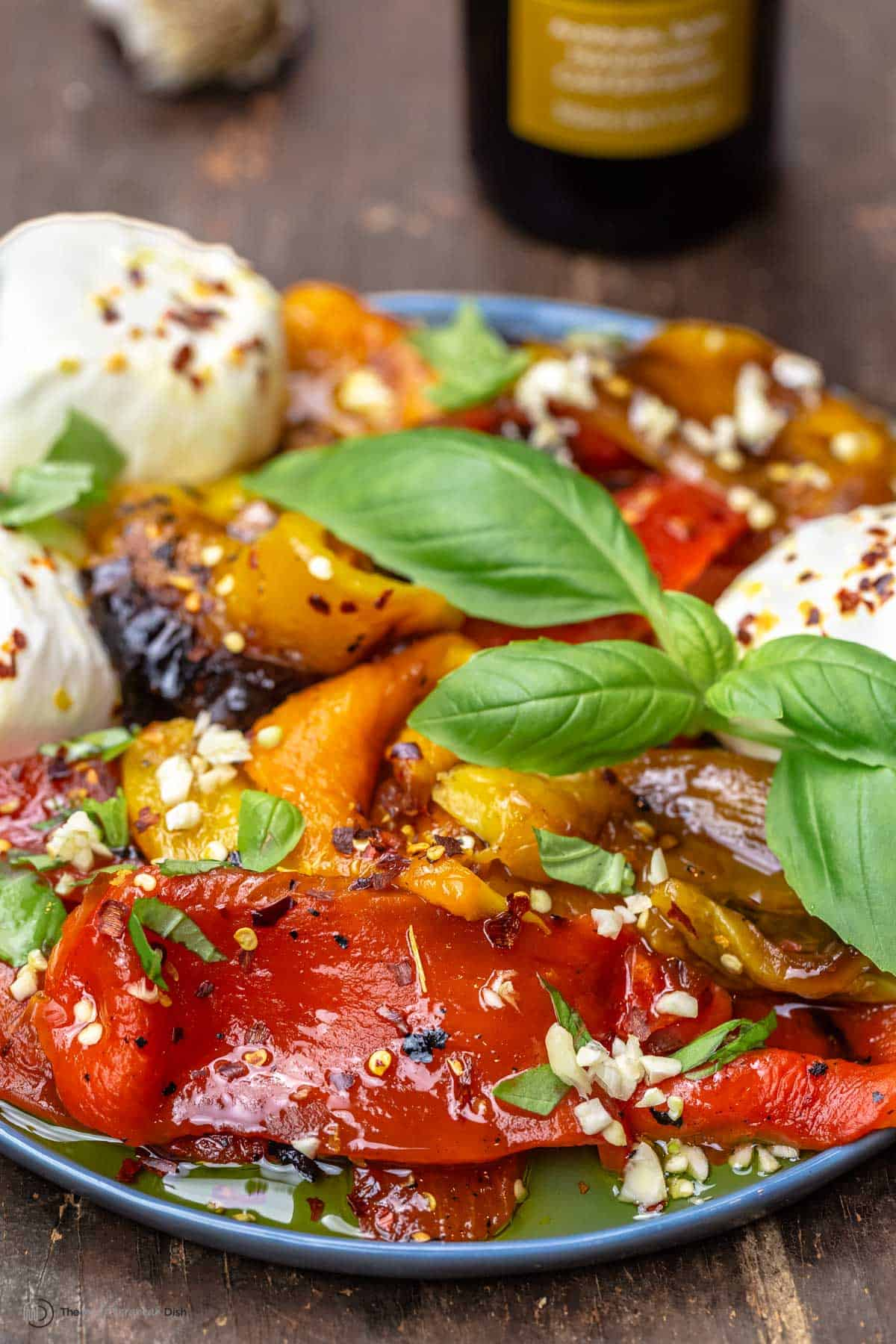 Roasted red peppers on a tray with burrata