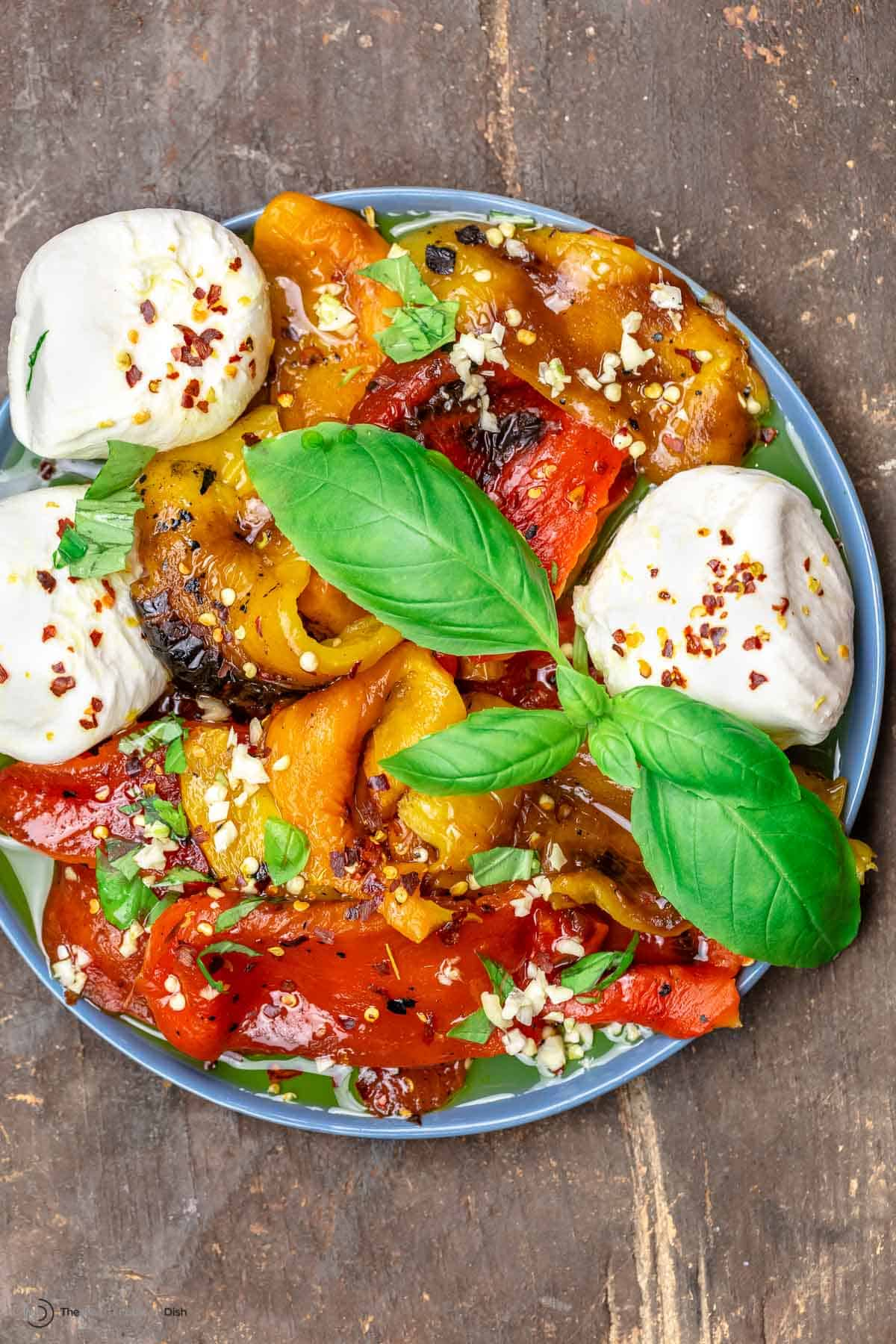 Roasted red peppers and burrata on a blue plate