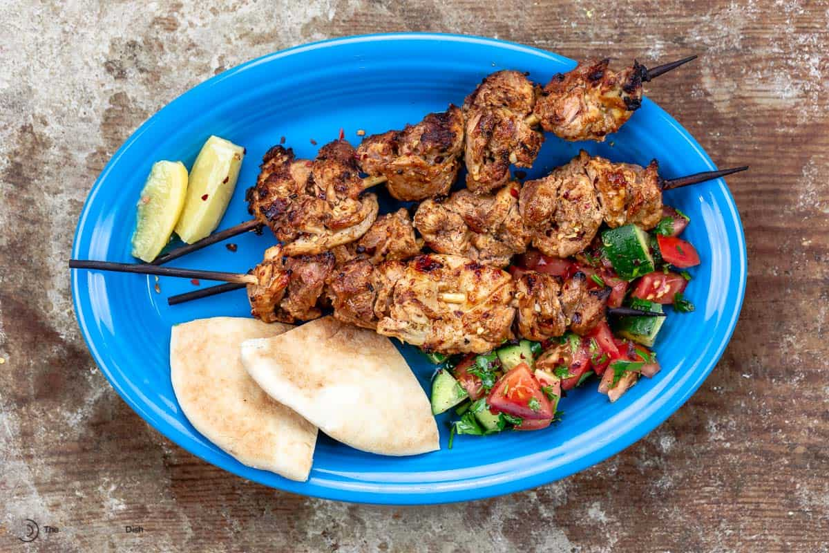 Shish tawook on a blue plate with pita