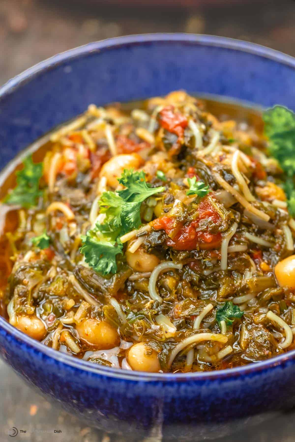 A blue bowl of Mediterranean spinach stew