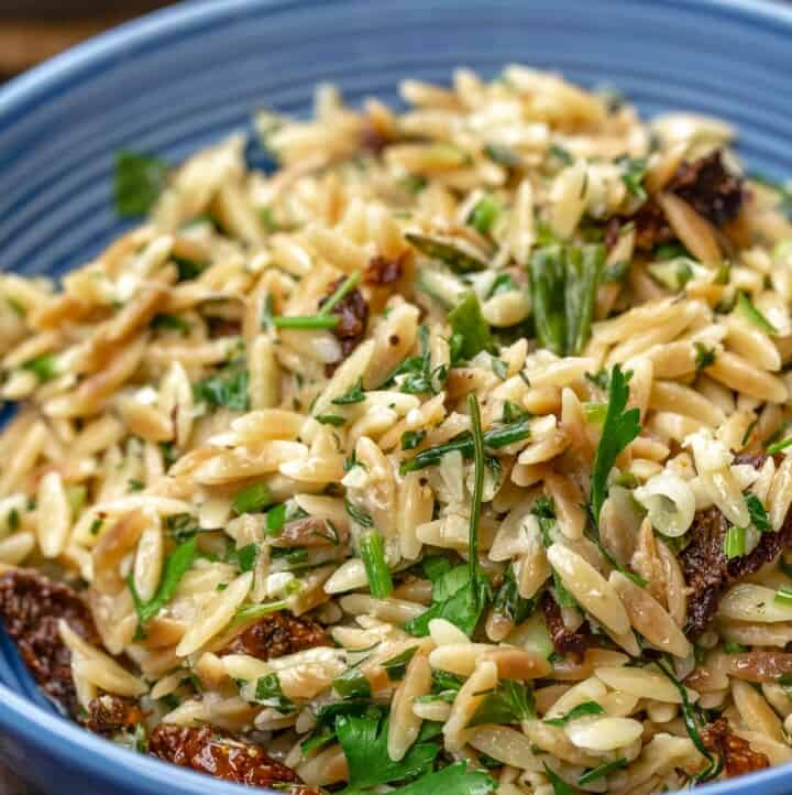 toasted orzo recipe served in blue bowl with sundried tomatoes and a garnish of parsley