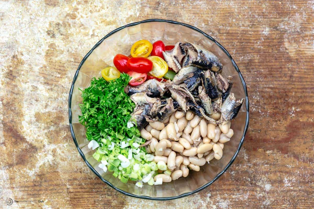White bean and sardine salad ingredients in a white bowl