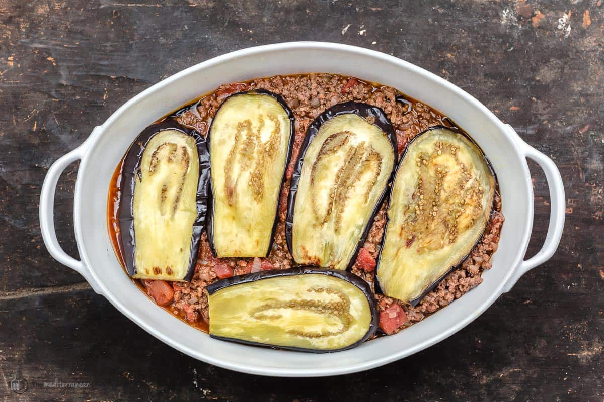 casserole dish with a layer of moussaka meat sauce and another layer of roasted eggplant