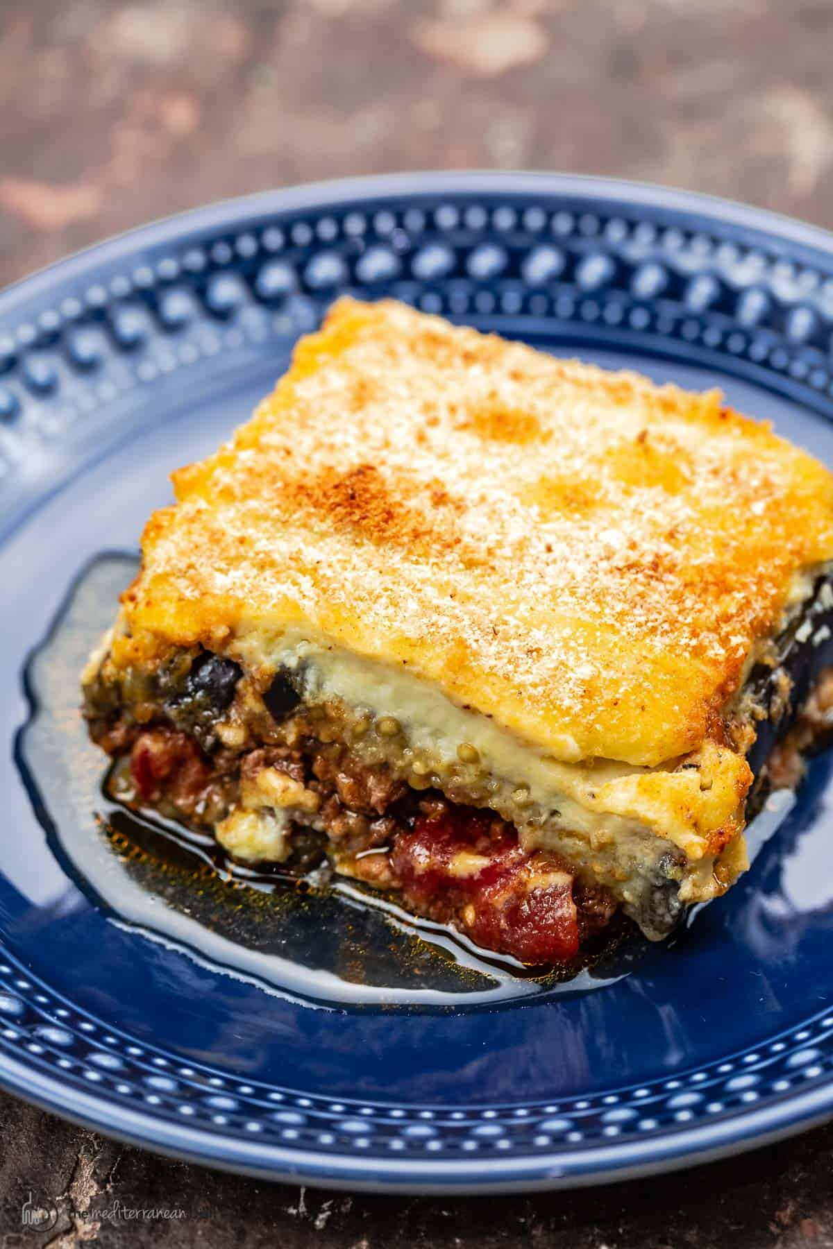 one slice of moussaka with eggplant, meat sauce, and bechamel on a blue plate