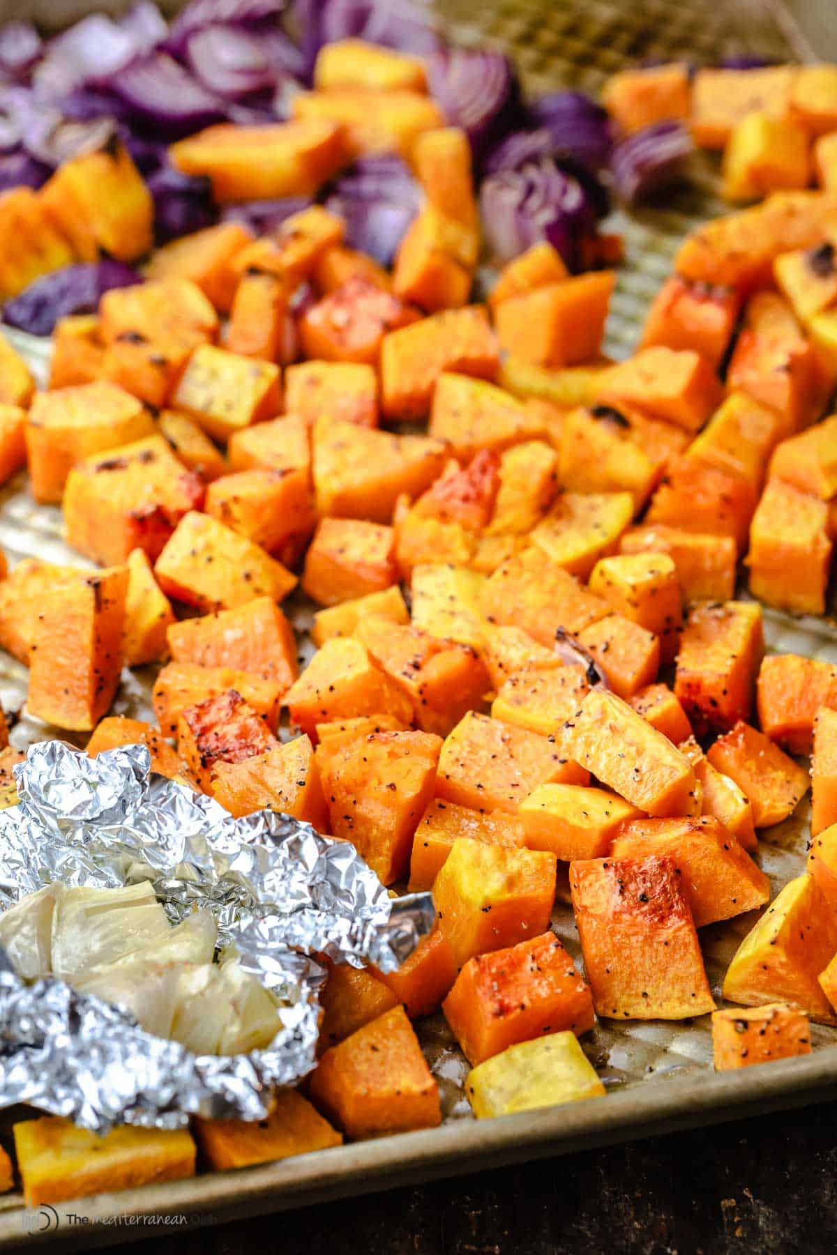 Roasted butternut squash pieces on a baking dish