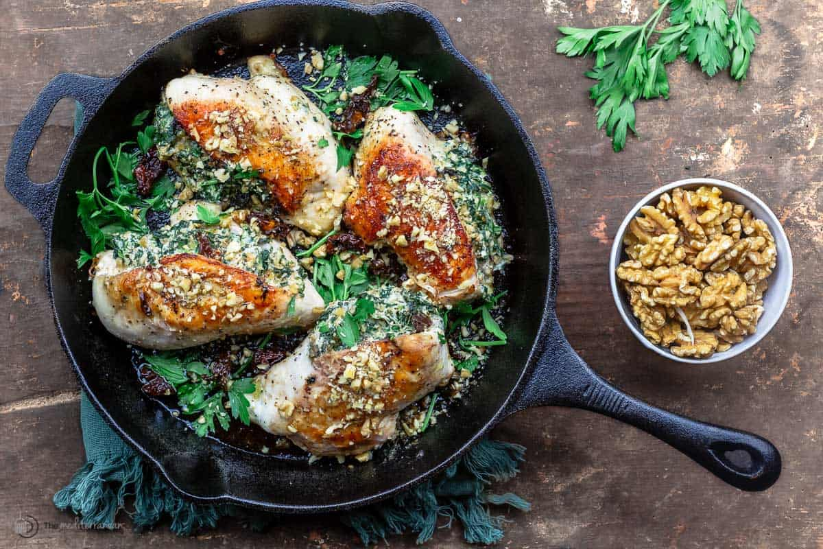 stuffed chicken breast in the skillet with a side bowl of walnuts