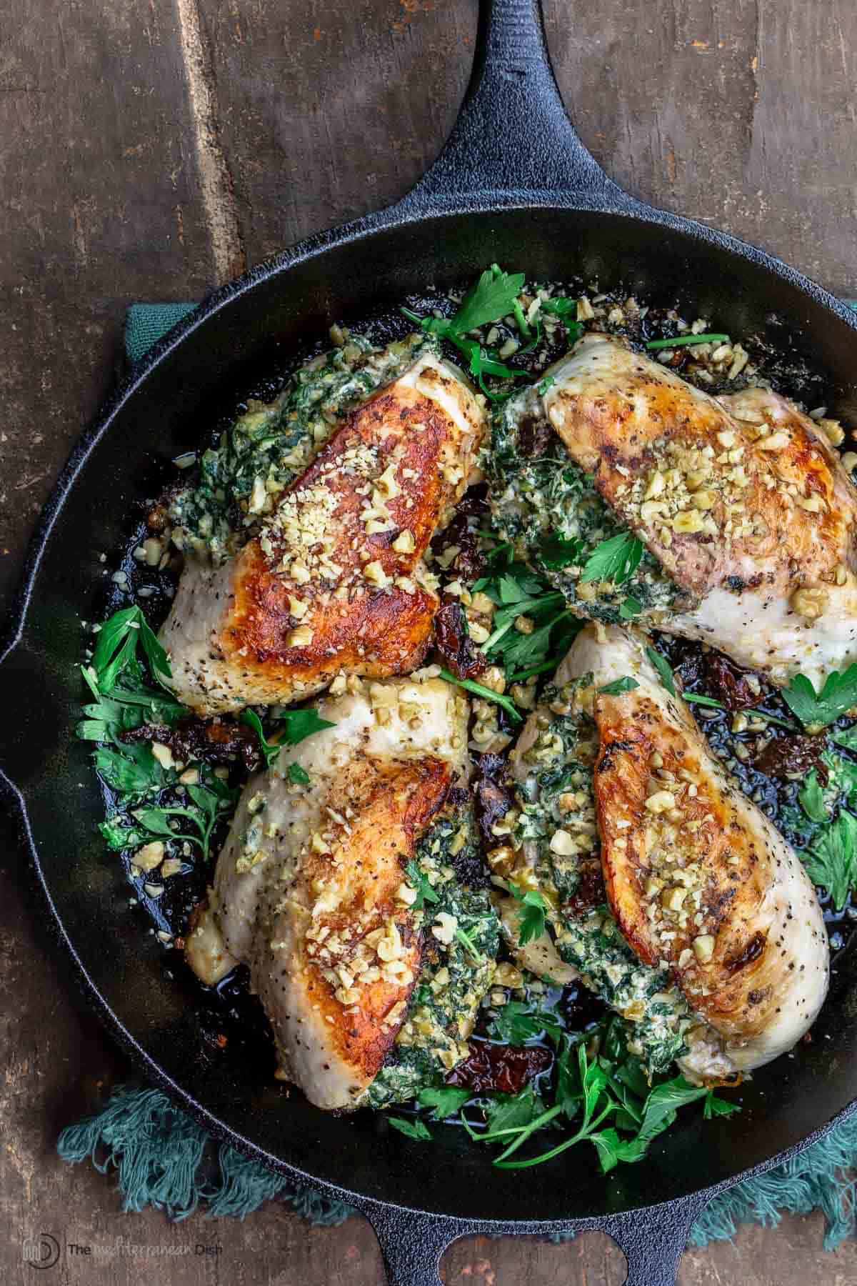 stuffed chicken breasts with spinach in a cast iron skillet