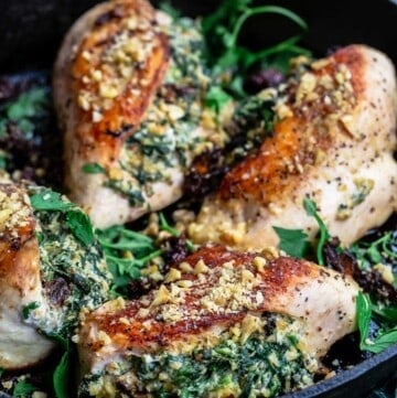 chicken breasts, stuffed with spinach, ricotta, and walnuts in a cast iron skillet